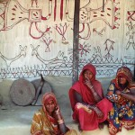 Nepal: Ranibati Mukhiya (far right) sitting with relatives and neighbors next to her wall painting, 1989. Photograph courtesy of Claire Burkert.
