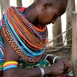 Kenya: Young Samburu woman beading a necklace strand in the Umoja Village, Kenya, 2000s. Photograph by Aaron Kisner, courtesy of Vital Voices.