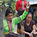 Lao PDR: A Tai Lue woman from Ban Na Nyang teaches spinning cotton to a Tai Dam woman from Phongsaly, 2010. Photograph by Jack Parsons.