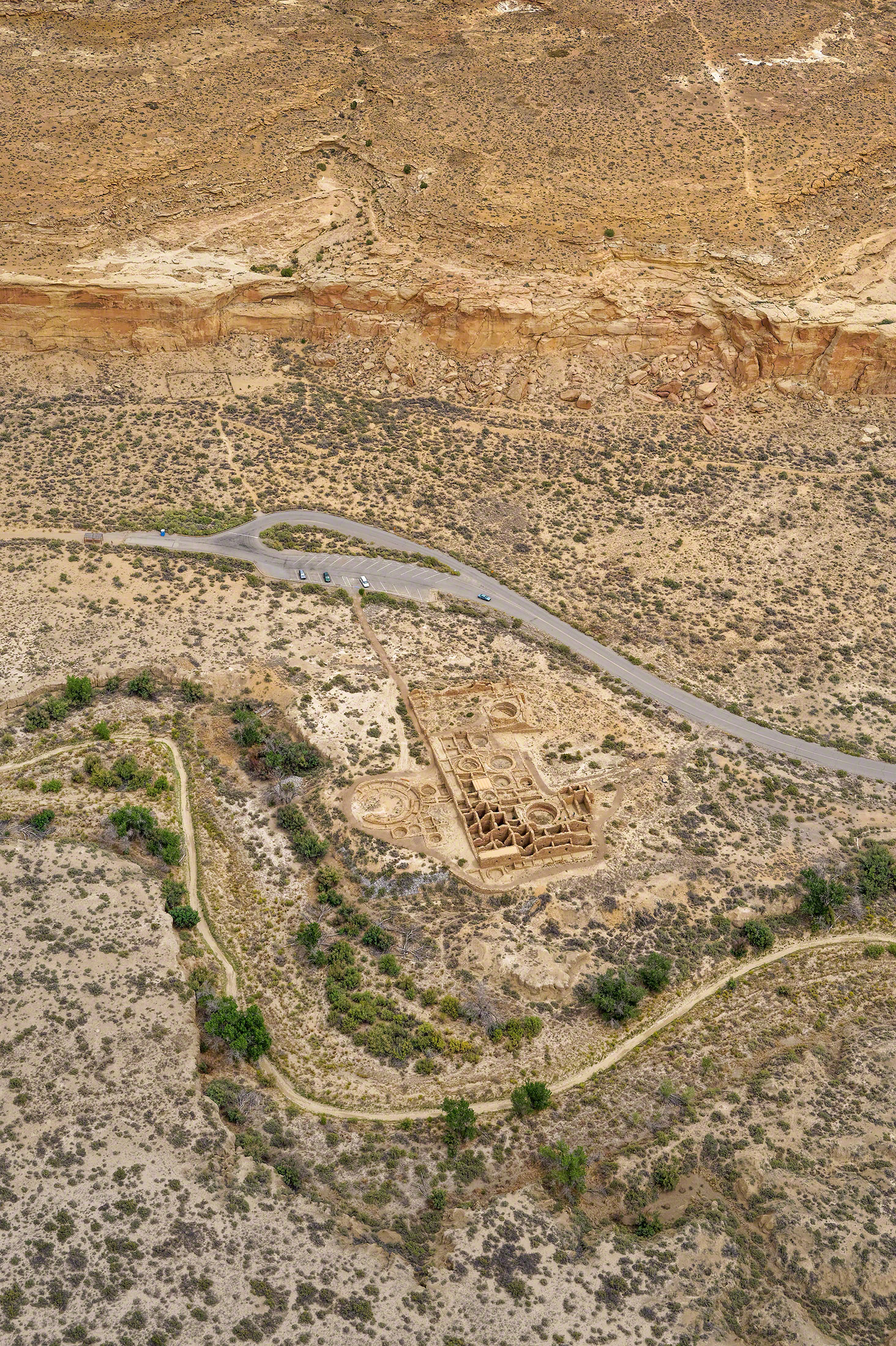 Oblique aerial view of Pueblo Del Arroyo along Chaco Wash in Chaco Canyon, looking north in midday light. This view is an attempt to rephotograph the 1929 aerial photograph by Charles Lindbergh, negative #130199.